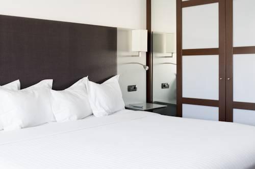 Biała pościel stanowiąca kontras dla szafy w hotelu AC Hotel by Marriott Zizur Mayor, Hiszpania