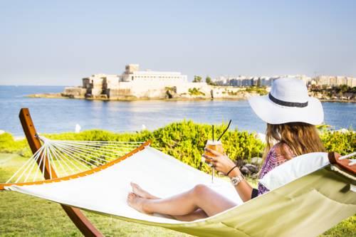 Kobieta na hamaku pijąca drinka w okolicy hotelu corinthia hotel st Georges bay