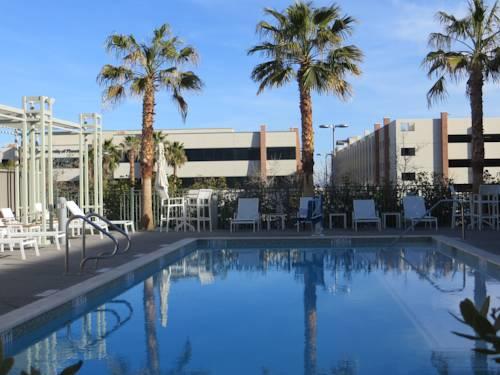 basen z białymi leżakami w hotelu oraz widok ma palmy