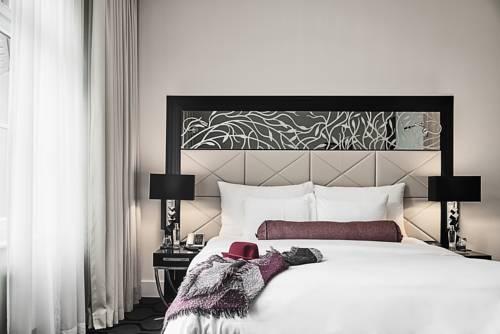 Pokoj dla dwojga utrzymany w białej tonacji z dodatkami czarnego w Hotel am Steinplatz, Niemcy