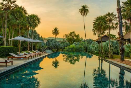 Leżaki i basen wśród palm w Indigo Pearl