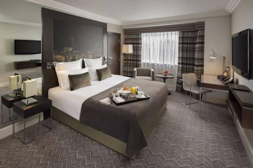 Pokój dla dwojga z tacą śniadaniową utrzymany w odcnienach brązu w hotelu Jumeirah Lowndes Hotel, Wielka Brytania