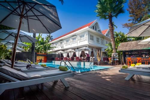 Miejsce relaksu nad basem na leżakach w hotelu Maison Souvannaphoum Hotel,, Laos