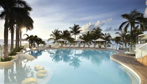 Basen rekreacyjny oraz palmy wraz z widokiem na morze w hotelu Mövenpick Hotel Mactan Island Cebu,
