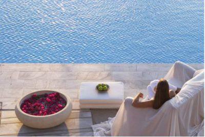 Kobieta, która odpoczywa nad brzegiem basenu i czeka na zabiegi spa w hotelu Yria Resort