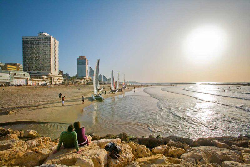 plaża w pełnym słońcu, przy brzegu żaglówki, w tle budynki miasta, Telawiw