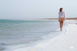 młoda kobieta spacerująca boso brzegiem Morza Martwego w wietrzny dzień