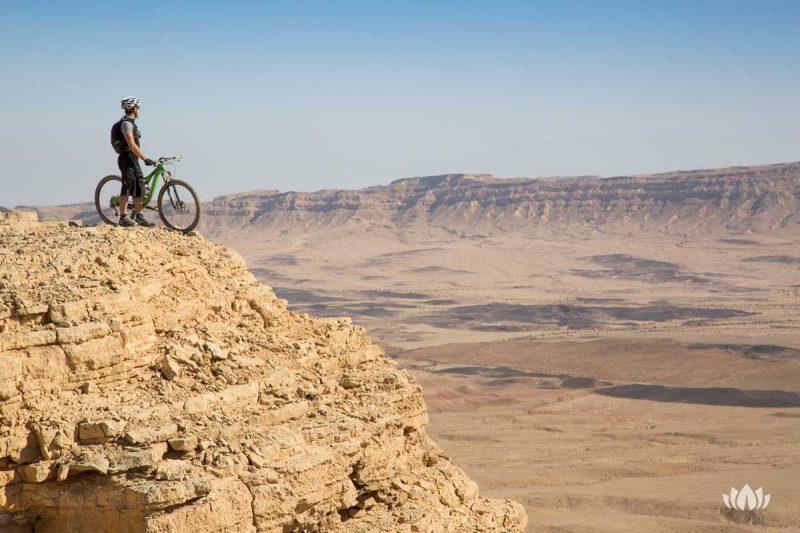 rowerzysta na wzniesieniu podziwiający widoki na pustynii w Izraelu