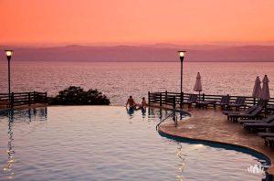 para nad brzegiem basenu z widokiem na morze podczas zachodu słońca, Jordania
