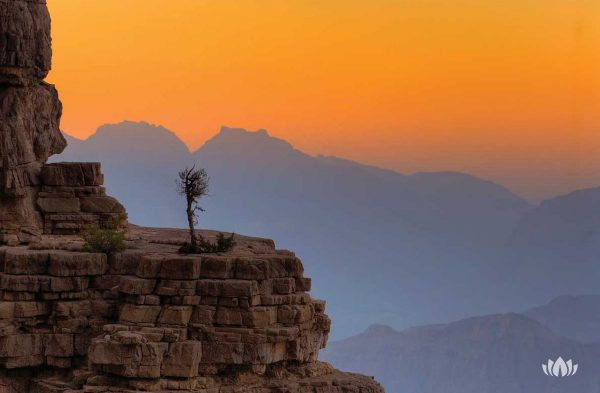 widok ze szczytu na oświetlone zachodzącym słońcem góry w Omanie
