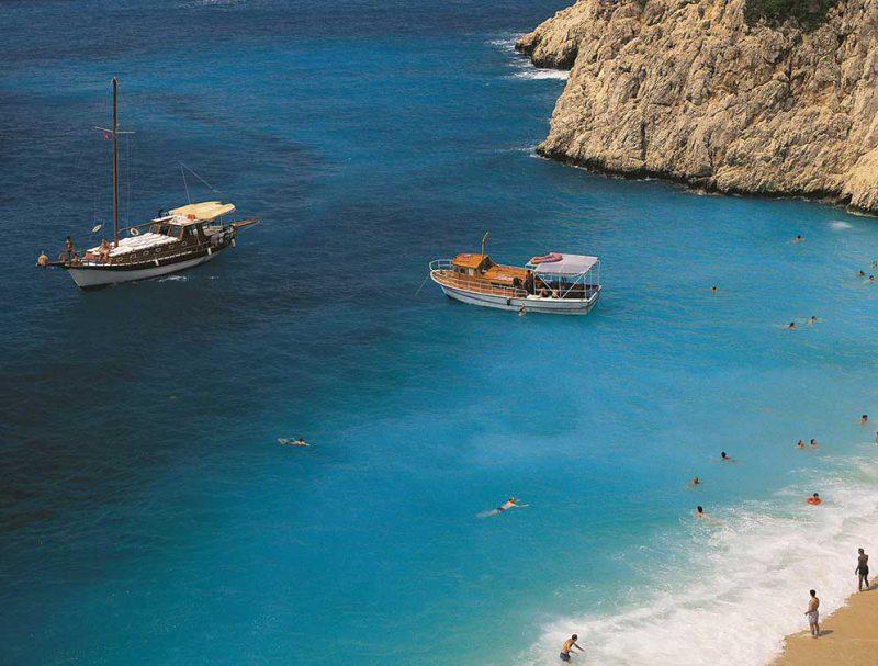 widok ze wzniesienia na plażę w Antayli, kąpiących się w morzu turystów i pływające statki