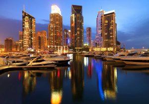 oświetlony nocą port w Dubaju, w tle panorama miasta