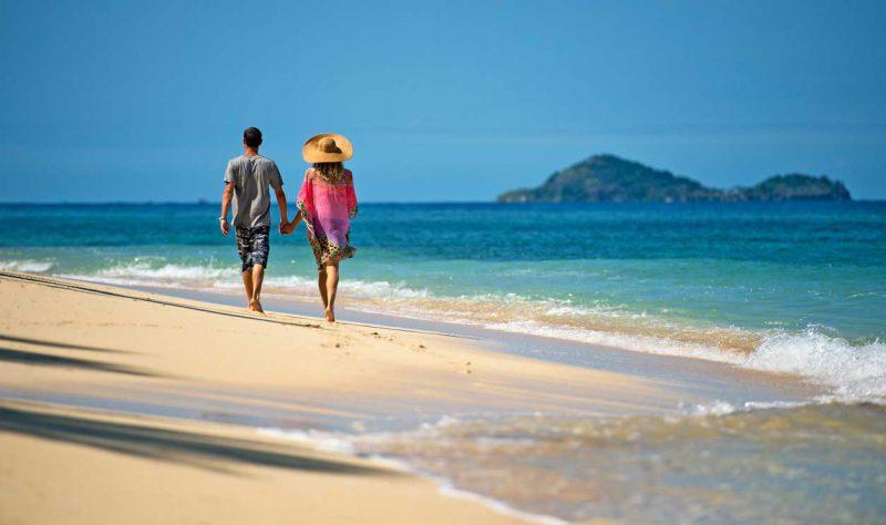 para spacerująca boso za rękę brzegiem błękitnego oceanu
