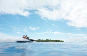 para turystów opływająca w ciepły słoneczny dzień skuterem wodnym małą wysepkę położoną na Fidżi