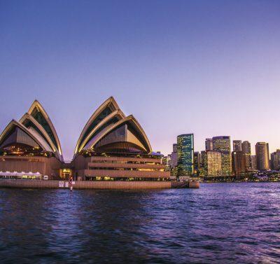 widok z zewnątrz na położoną nad wodą operę w Sydney późnym wieczorem