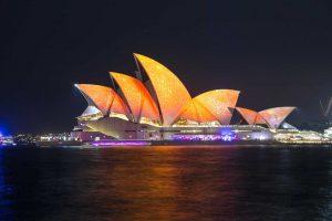 oświetlona nocą Opera w Sydney położona nad brzegiem oceanu