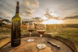 dwa kieliszki i butelka wina na tacy na tle zachodzącego słońca
