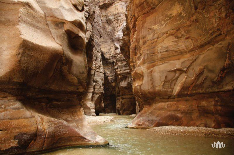 rzeka Wadi Mujib płynąca wąskim korytarzem między wysokimi skałami, Jordania
