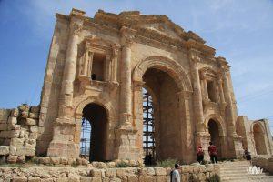widok na turystów podziwiających w słoneczny dzień łuk Hadriana w Jordanii