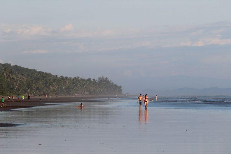 para spacerująca wzdłuż szerokiej plaży brzegiem morza, Kostaryka