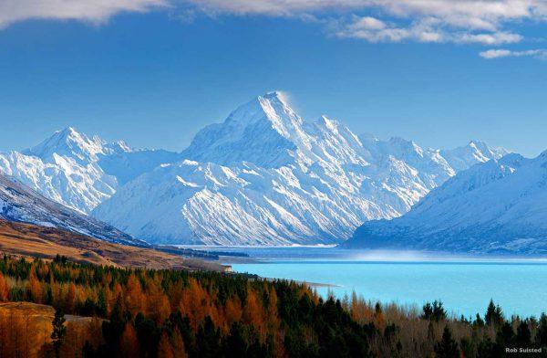 widok z oddali na ogromną ośnieżoną górę Aoraki w Nowej Zelandii, u pondóża góry jezioro