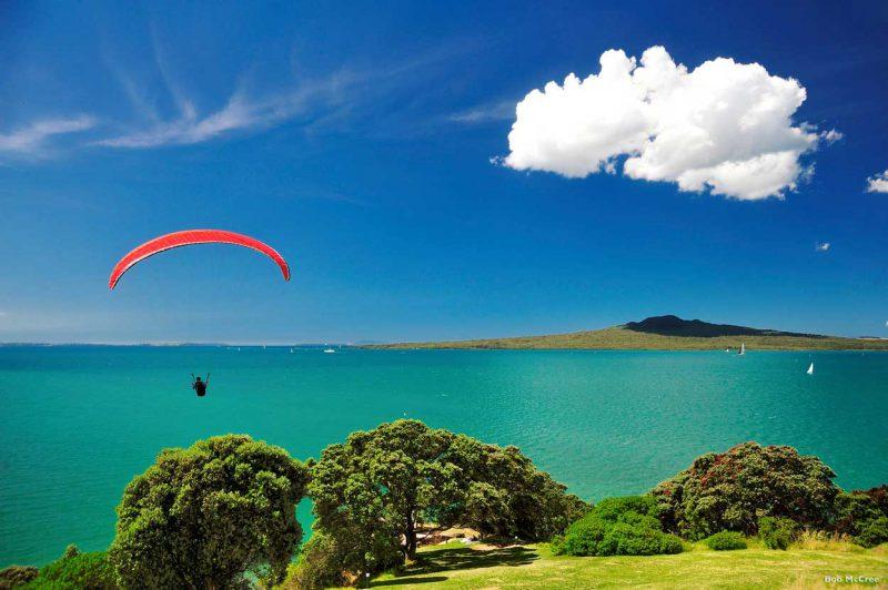 paralotniarz unoszący się nad błętkitną wodą Hauraki Gulf w Nowej Zelandii