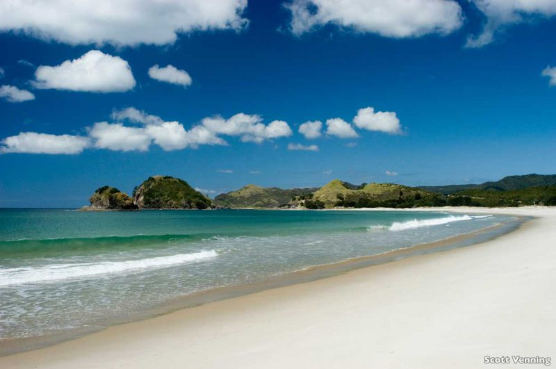 brzeg piaszczystej plaży Kaitoke Beach, w tle łagodne wzniesienia