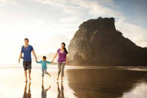 rodzina spacerująca boso w słoneczny dzień brzegiem plaży Piha Beach, w tle skały