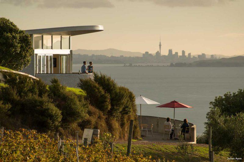 grupa ludzi pijąca wino w restauracji nad brzegiem