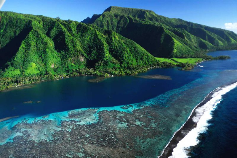 widok z lotu ptaka na kolorową rafę i zieloną wyspę o bujnej roślinności, Polinezja