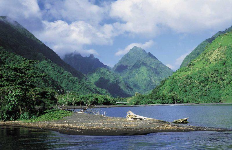 wysokie, pokryte zielenią, otoczone chmurami szczyty gór Tahiti położone nad oceanem