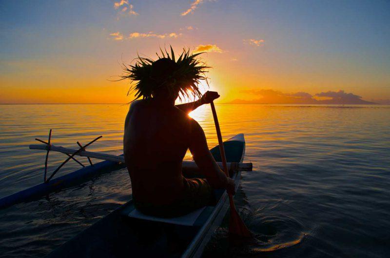 mieszkaniec Polinezji płynący kajakiem na tle zachodzącego słońca
