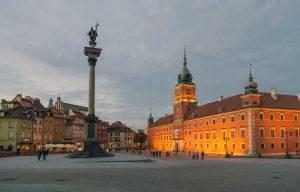 widok na plac zamkowy w Warszawie, oświetlony wieczorem Zamek Królewski