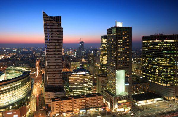 widok z lotu ptaka na centrum Warszawy oświetlone nocą, w tle wysokie wieżowce