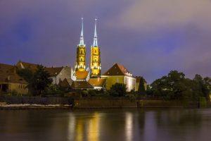 widok z brzegu rzeki na oświetlony nocą kościół we Wrocławiu