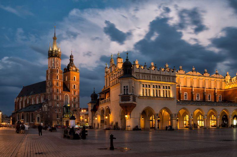 widok z rynku na oświetlone sukiennice w Krakowie, w tle kościół Mariacki