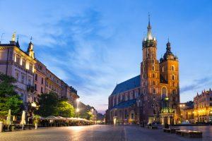 oświetlony późnym wieczorem zamek Mariacki widziany z rynku w Krakowie