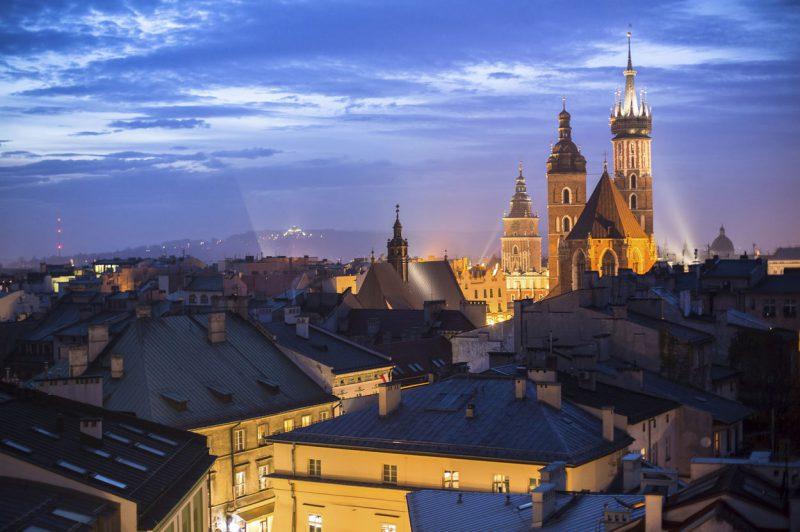 wieczorne miasto Kraków z widocznym oświetlonym kościołem Mariackim, w tle panorama miasta