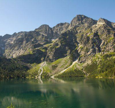 widok na staw położony u szczytu gór w Tatrach