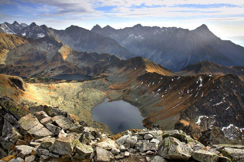 widok ze szczytu na położone poniżej dwa stawy w Tatrach, w tle inne szczyty