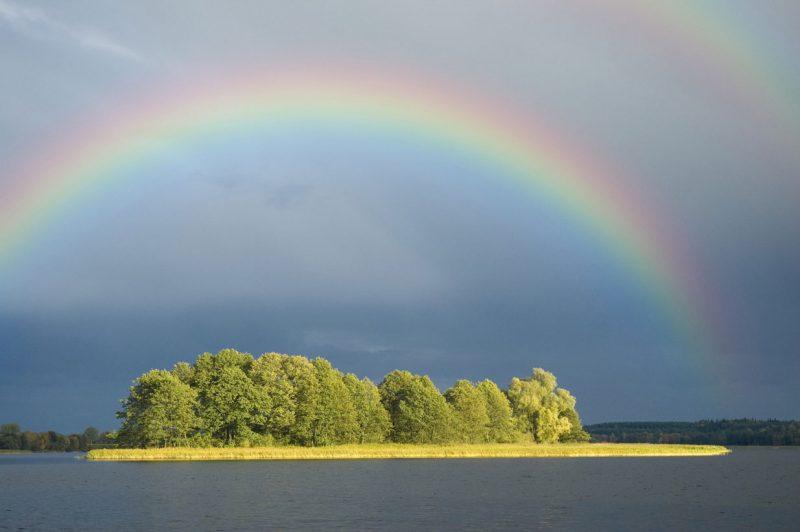 ogromna tęcza wschodząca na pochmurnym niebie nad wyspą na mazurskim jeziorze
