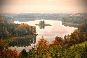 jesienny widok z lotu ptaka na jezioro mazurskie otoczone barwnymi lasami