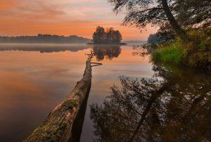 romantyczny krajobraz mazurskiego jeziora pokrytego mgłą, w tle lasy
