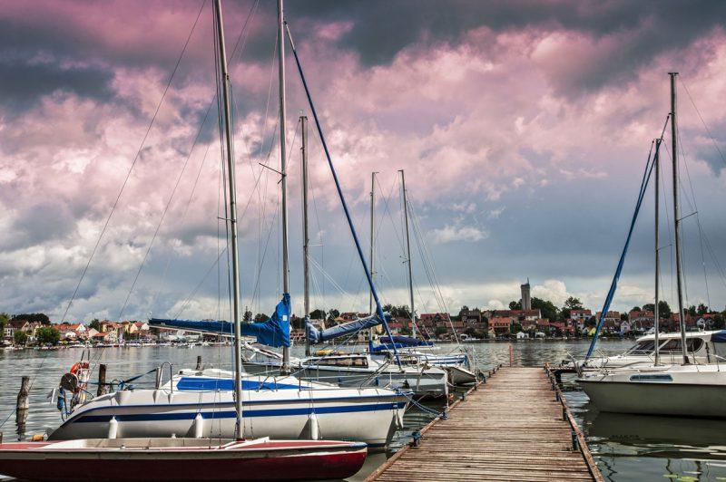 łódki zacumowane przy pomoście nad mazurskim jeziorem, w tle budynki miasta