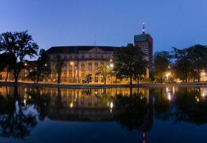 widok na położony nad wodą, oświetlony nocą budynek Uniwersytetu Ekonomicznego w Poznaniu