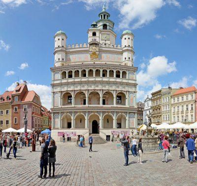 widok z zewnątrz na ratusz miasta Poznań, w tle tłum turystów zwiedzający rynek