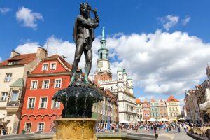 fontanna Apolla w Poznaniu, w tle tłum turystów spacerujący między kolorowymi kamienicami