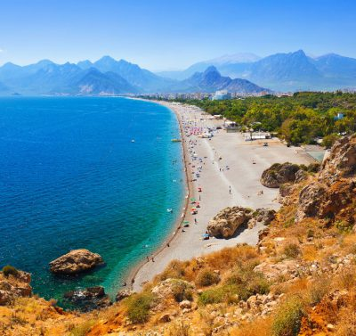 widok wzdłuż wybrzeża w Antalyi, turkusowa woda, szeroka piaszczysta plaża z turystami, w tle wysokie szczyty gór Taurus