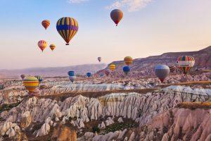 widok na liczne kolorowe balony z pasażerami, unoszące się nad Kapadocją