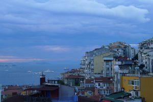 widok na wybrzeże w Stambule otoczone licznymi zabudowaniami, w tle statki pływające po morzu